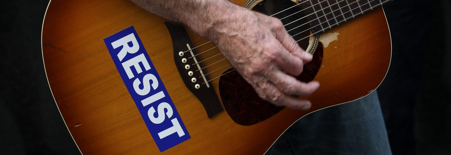 With his guitar adorned with a 'RESIST' sticker, a demonstrator plays music during a gathering to mark the 73rd anniversary of the Hiroshima and Nagasaki nuclear bombings, outside the Japanese Consulate in Midtown Manhattan, August 3, 2018 in New York City. (Photo by Drew Angerer/Getty Images)