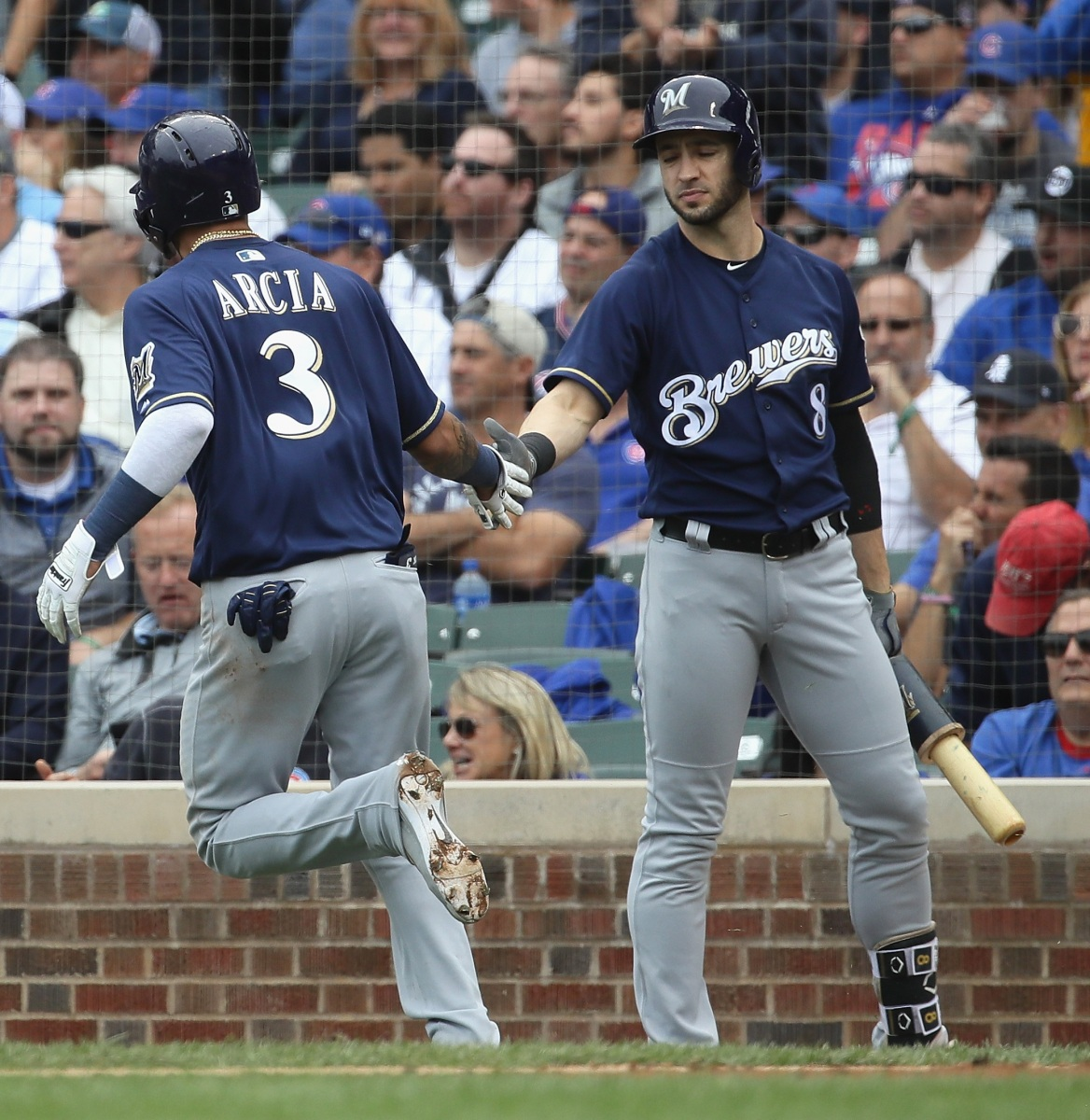 Orlando Arcia #3 of the Milwaukee Brewers is congratulated by Ryan Braun #8 after scoring a run in the 3rd inning against the Chicago Cubs during the National League Tiebreaker Game at Wrigley Field on October 1, 2018 in Chicago, Illinois. (Photo by Jonathan Daniel/Getty Images)