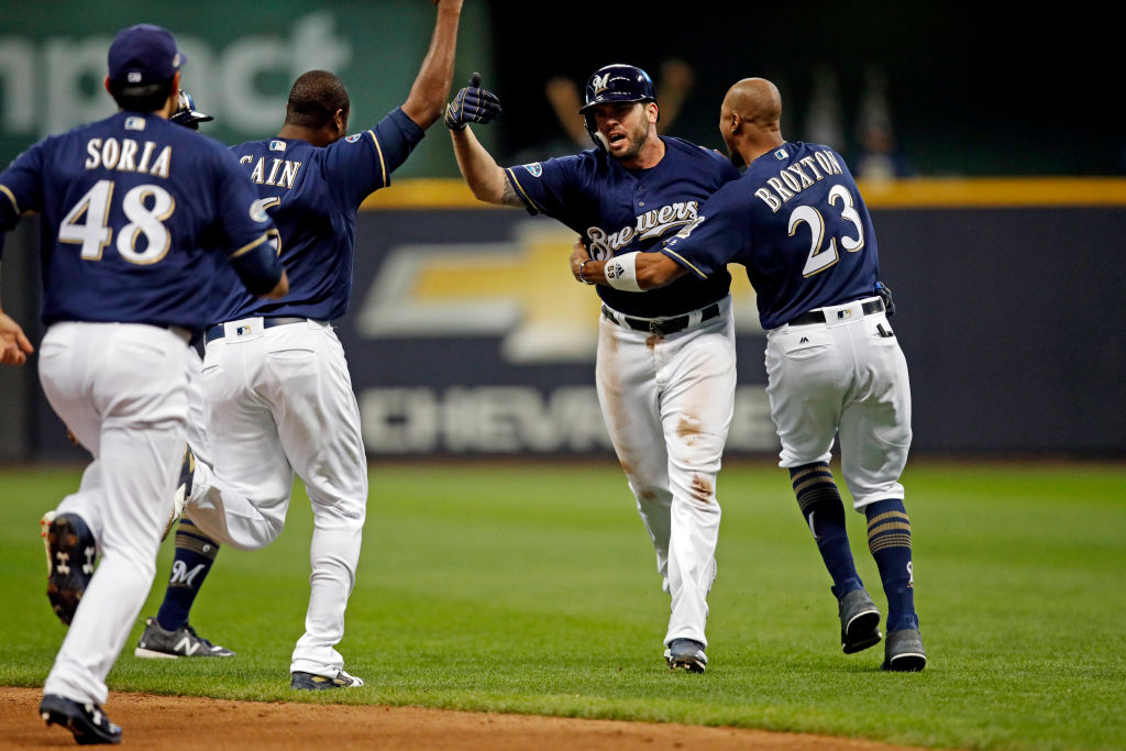 MILWAUKEE, WI - OCTOBER 4:  Mike Moustakas #18 of the Milwaukee Brewers celebrates with teammates after hitting the game-winning RBI single in the ninth inning to beat the Colorado Rockies in Game 1 of the NLDS at Miller Park on Thursday, October 4, 2018 in Milwaukee, Wisconsin. (Photo by Mike McGinnis/MLB Photos via Getty Images)