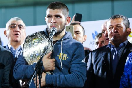 UFC lightweight champion Khabib Nurmagomedov (C) with father and coach Abdulmanap Nurmagomedov (R) address supporters at Anzhi Arena Stadium after defending his UFC title by defeating Irish MMA fighter Conor McGregor at the UFC 229 tournament. Musa Salgereyev/TASS (Photo by Musa SalgereyevTASS via Getty Images)