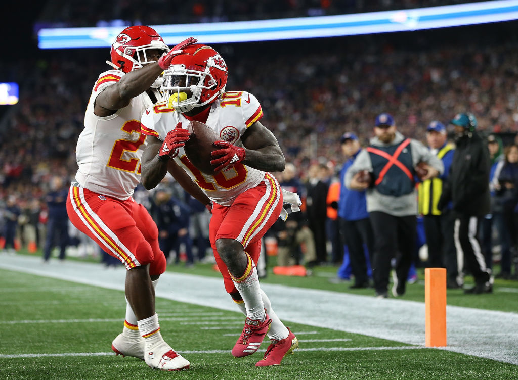 Tyreek Hill #10 of the Kansas City Chiefs celebrates a touchdown pass with Kareem Hunt #27 of the Kansas City Chiefs against the  New England Patriots in the fourth quarter at Gillette Stadium on October 14, 2018 in Foxborough, Massachusetts. (Photo by Jim Rogash/Getty Images)