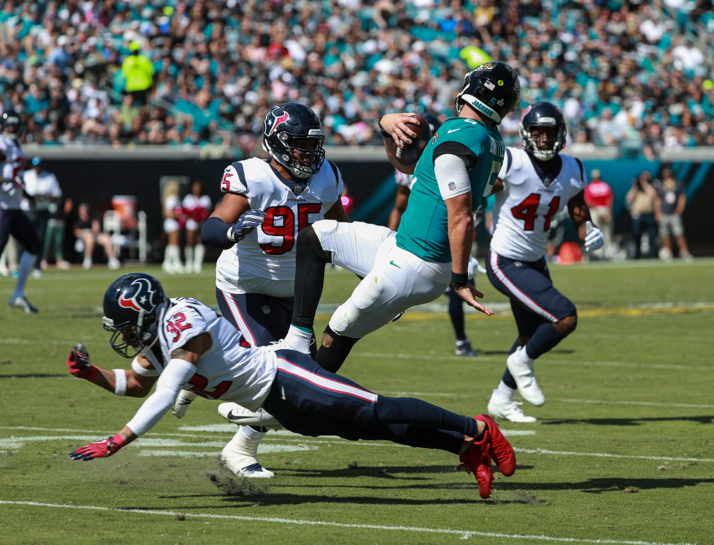 Blake Bortles #5 of the Jacksonville Jaguars is brought down by members of the Houston Texans defense during the second half at TIAA Bank Field on October 21, 2018 in Jacksonville, Florida.  (Photo by Scott Halleran/Getty Images)