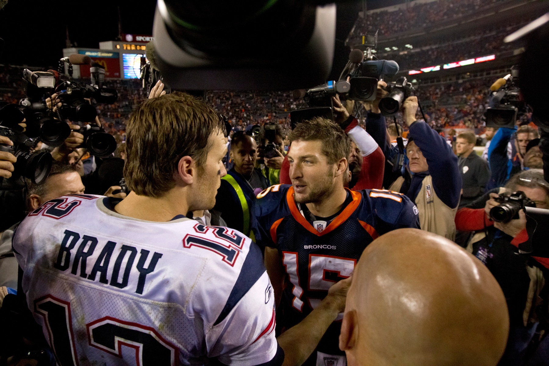 New England Patriots Tom Brady and Denver Broncos Tim Tebow meet after the Patriots defeated the Broncos 41-23 at Sports Authority Field on Sunday, Dec. 18, 2011. (Photo by Matthew J. Lee/The Boston Globe via Getty Images)
