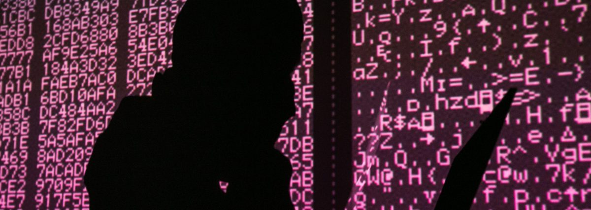 A silhouette of a man in a balaclava mask sitting at a laptop computer, with computer code in the background. Sergei Konkov/TASS (Photo by Sergei KonkovTASS via Getty Images)