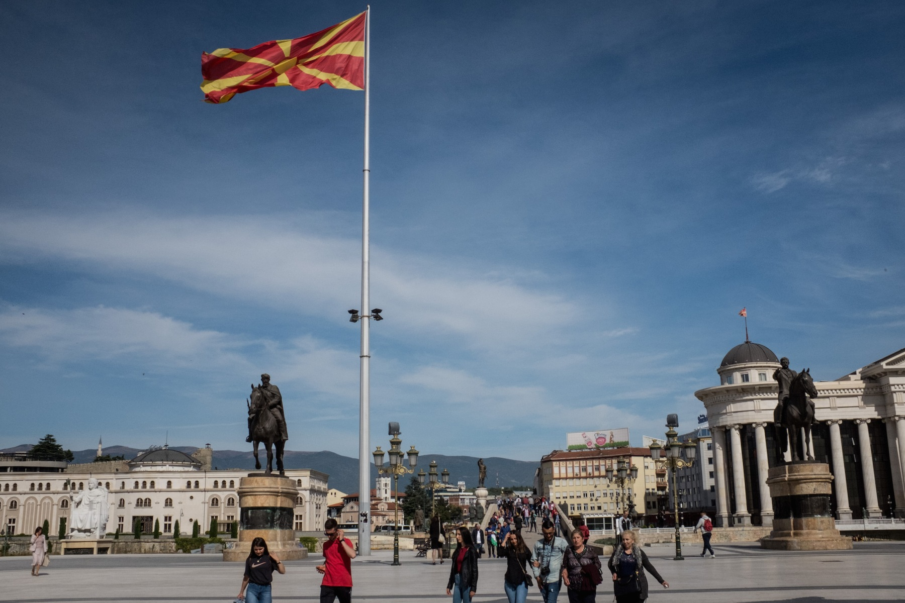 """People walk under a larg Macedonian flag on September 28, 2018 in Skopje, Macedonia. Macedonians will go to the polls Sunday to vote in a referendum to change the countries name to the """"Republic of North Macedonia"""" and end a long running dispute with Greece. Macedonia would not be the first country in recent memory to change its name. (Photo by Chris McGrath/Getty Images)"""