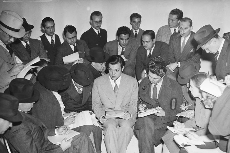 [Original caption] Actor Orson Welles explains the radio broadcast of H.G. Wells' 'The War of the Worlds' to reporters after it caused widespread panic. (Getty Images)