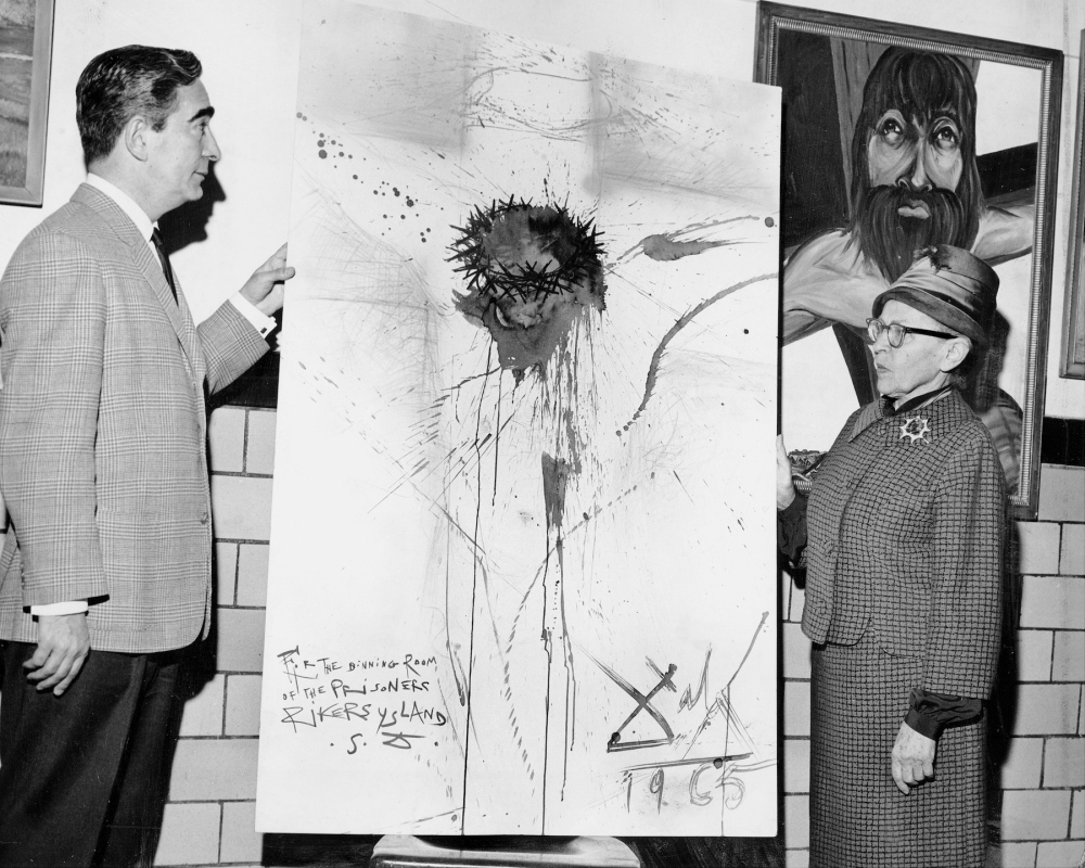 """Nico Yperifanos, Salvador Dali's personal representative, presents artist's 'Christ on the Cross"""" to Rikers Island prison. Correction Commissiojner Anna Kross accepts the work. The Dali painting was stolen by prison guards in 2003. (Photo by Leonard Detrick/NY Daily News Archive via Getty Images)"""