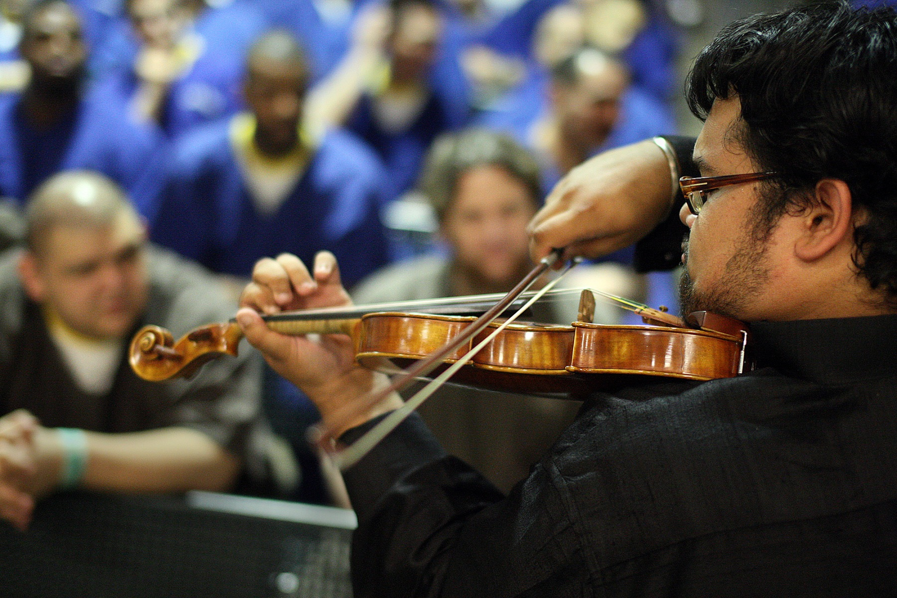 """Prison inmates, part of the M.E.R.I.T. (Maximizing Education Reaching Individual Transformation) Program, listen to Vijay Gupta play the violin as part of a summer concert performed by """"Street Symphony"""" at the Men's Central Jail in Los Angeles on August 29, 2012. Gupta recently received a 2018 MacArthur genius grant. (Photo by Gary Friedman/Los Angeles Times/Getty Images)"""