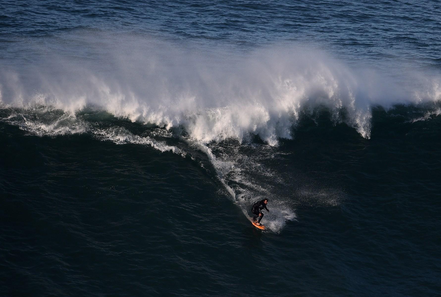 Brazilian big wave surfer Rodrigo Koxa drops a wave at Nazare's North Beach on November 29, 2014.   AFP PHOTO/ FRANCISCO LEONG        (Photo credit should read FRANCISCO LEONG/AFP/Getty Images)