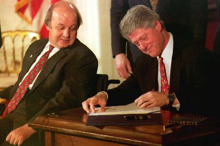 WASHINGTON, DC - NOVEMBER 30:  James Brady (L), the Reagan Administration press secretary who was wounded during the 1981 attempted assassination of then President Ronald Reagan, watches as U.S. President Bill Clinton signs the Brady Bill at the White House 30 November 1993. (PAUL RICHARDS/AFP/Getty Images)