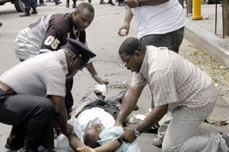 Police and pedestrians help a man wounded 11 July, 2005 after an explosive artifact exploded in a busy shopping district in downtown Port-of-Spain, Trinidad and Tobago, wounding 13 people. Police have yet to confirm if the blast was caused by a bomb or a hand grenade thrown into the bin, as some eyewitness reported.  AFP PHOTO STR   MAXIMUM QUALITY AVAILABLE  TRINIDAD AND TOBAGO OUT  (Photo credit should read STR/AFP/Getty Images)