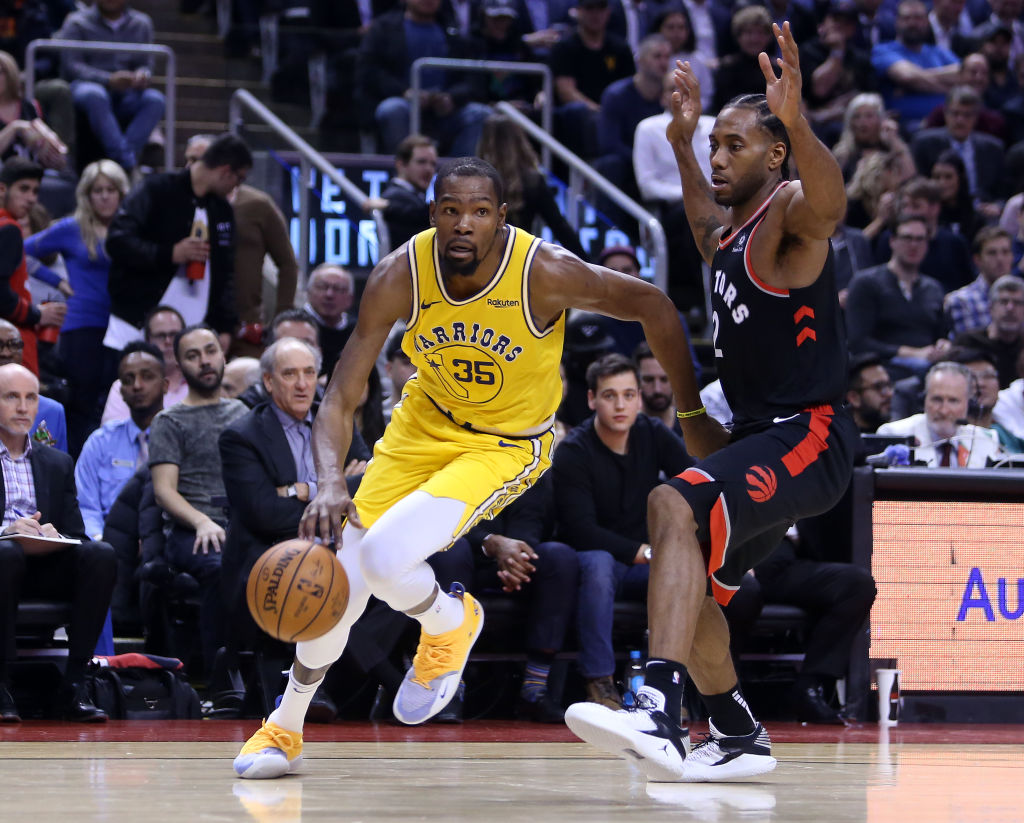 TORONTO, ON - NOVEMBER 29:  Kevin Durant #35 of the Golden State Warriors dribbles the ball as Kawhi Leonard #2 of the Toronto Raptors defends during the second half of an NBA game at Scotiabank Arena on November 29, 2018 in Toronto, Canada. (Photo by Vaughn Ridley/Getty Images)