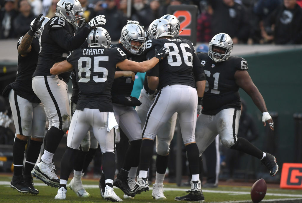 OAKLAND, CA - DECEMBER 09:  Derek Carr #4 of the Oakland Raiders (C) celebrates with teammates after he threw a touchdown pass against the Pittsburgh Steelers during the second half of an NFL football game at Oakland-Alameda County Coliseum on December 9, 2018 in Oakland, California.  (Photo by Thearon W. Henderson/Getty Images)
