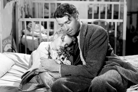 American actors James Stewart (1908 - 1997), as George Bailey, and Karolyn Grimes as his daughter Zuzu, in a scene from 'It's a Wonderful Life', directed by Frank Capra, 1946. (Getty Images)