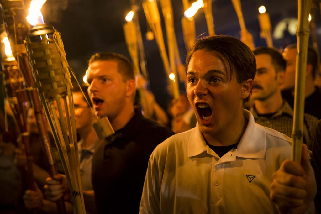 Peter Cvjetanovic (R) along with Neo Nazis, Alt-Right, and White Supremacists encircle and chant at counter protestors at the base of a statue of Thomas Jefferson after marching through the University of Virginia campus with torches in Charlottesville, Va., USA on August 11, 2017. (Photo by Samuel Corum/Anadolu Agency/Getty Images)