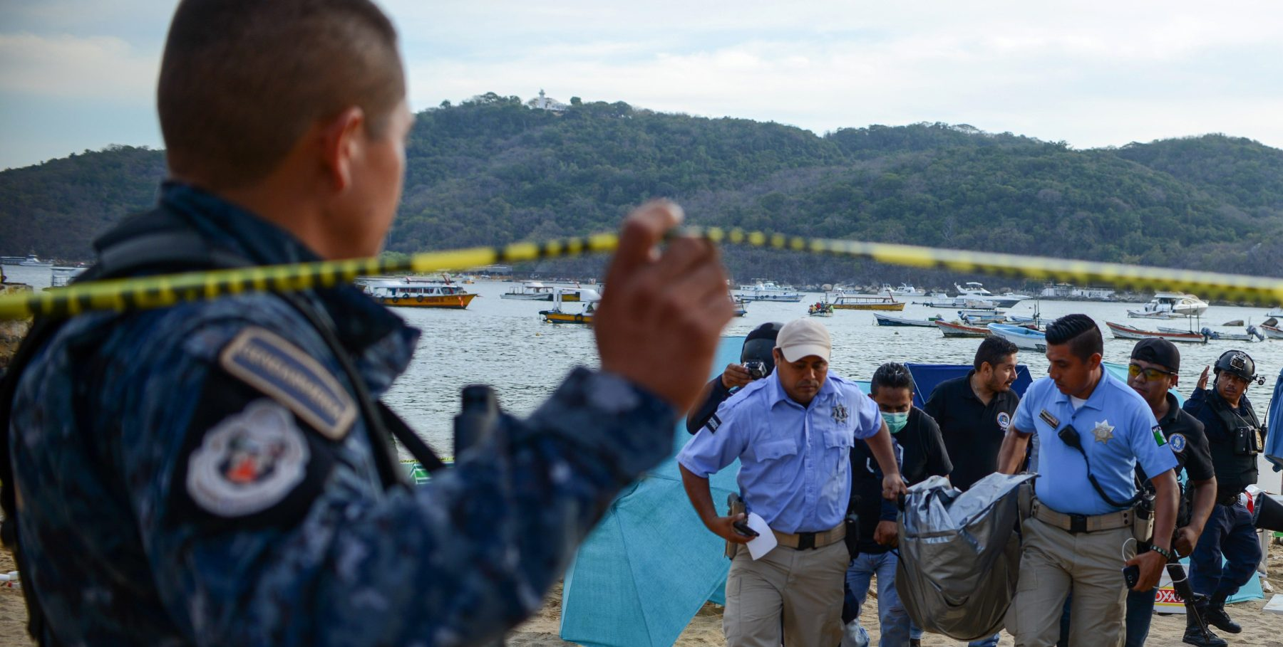 Forensic personnel and police officers carry the body of a murdered man, at Caletilla beach, in the touristic city of Acapulco, Guerrero State, Mexico, on March 18, 2018. Guerrero is one of Mexico's poorest and most violent states, where a lucrative drug trade has flourished. (FRANCISCO ROBLES/AFP/Getty Images)
