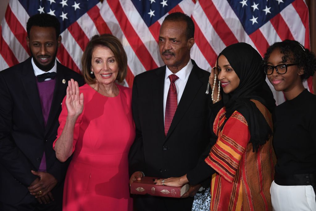 US House Representative Ilhan Omar (2nd-R), D-MN, with her hand on the Quran, participates in a ceremonial swearing-in with Speaker of the House Nancy Pelosi (2nd-L), D-CA,  during the start of the 116th Congress at the US Capitol in Washington, DC, January 3, 2019. (Photo by SAUL LOEB / AFP)        (Photo credit should read SAUL LOEB/AFP/Getty Images)
