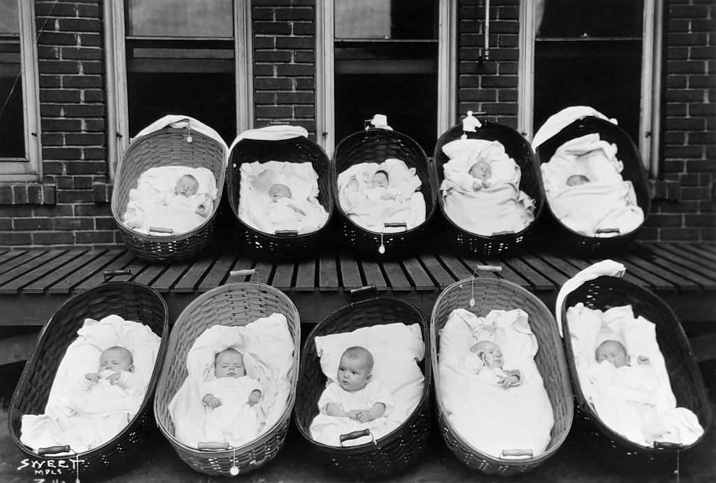 Ten babies, all but one sleeping, rest in baskets on a porch outside of a maternity ward. (Photo by © Minnesota Historical Society/CORBIS/Corbis via Getty Images)