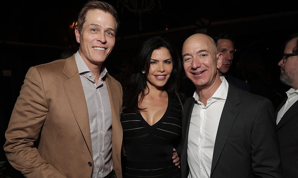 """Lauren Sanchez poses with her then-husband Patrick Whitesell (left), and future lover, Amazon CEO Jeff Bezos, at Jeff Bezos and Matt Damon's """"Manchester By The Sea"""" Holiday Party on December 3, 2016 in Los Angeles, California.  (Photo by Todd Williamson/Getty Images for Amazon Studios)"""
