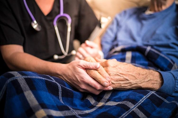 A hospice nurse visits an elderly patient. (Getty Images)