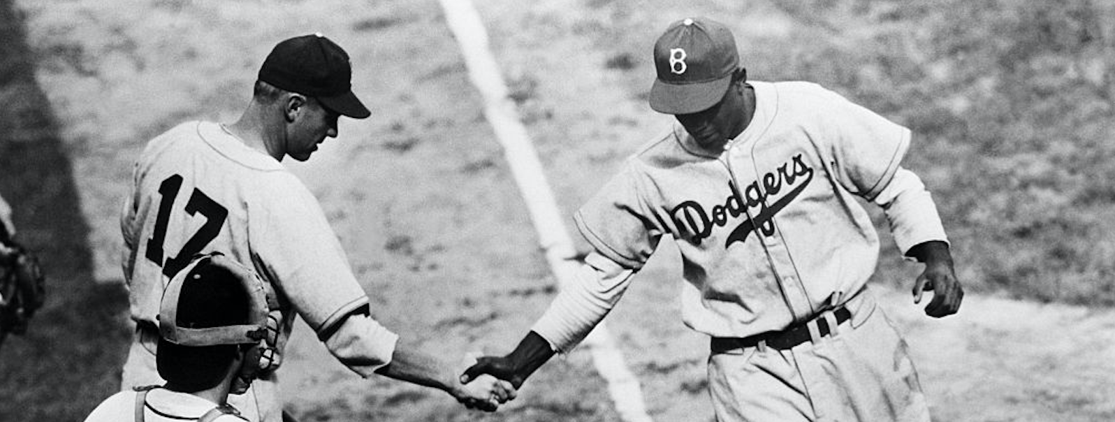 Jackie Robinson (right) of the Brooklyn Dodgers, breaking the color barrier this season as the first African-American to play in the Major Leagues, crosses home plate after hitting his first home run as a Dodger, off New York Giants' pitcher Dave Rosolo. Teammate Tommy Tatum, next up to bat, offers a congratulatory handshake as Giants catcher Walker Cooper looks on. The Giants opened their home season at the Polo Grounds with a victory over the Dodgers.