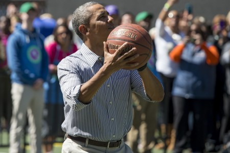 "US President Barack Obama shoots a basketball during the annual White House Easter Egg Roll on the South Lawn of the White House in Washington, DC, April 21, 2014. The 126th annual White House Easter Egg Roll, the largest annual public event at the White House with more than 30,000 attendees expected, features live music, sports courts, cooking stations, storytelling and Easter egg rolling, with the theme, ""Hop into Healthy, Swing into Shape."" AFP PHOTO / Saul LOEB        (Photo credit should read SAUL LOEB/AFP/Getty Images)"