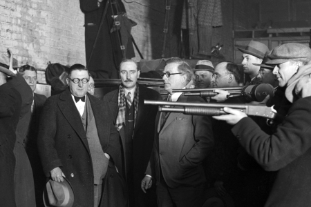 UNITED STATES - FEBRUARY 01: Police reenactment of the St. Valentine's Day Massacre, also known as the Moran Gang Massacre, when reputed members of the Al Capone gang disguised themselves as policemen and murdered members of the George 'Bugs' Moran gang in a garage at 2122 North Clark Street in the Lake View community area of Chicago, Illinois. Dr. Herman N. Bundesen, Cook County Coroner, is standing next to the men holding the rifles. (Photo by Chicago Sun-Times/Chicago Daily News collection/Chicago History Museum/Getty Images)