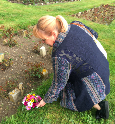 """Author Jo Vigor-Mungovin leaves flowers at the unmarked grave of """"Elephant Man"""" Joseph Merrick, which she recently discovered in the City of London Cemetery. (Screenshot: Twitter)"""