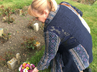 "Author Jo Vigor-Mungovin leaves flowers at the unmarked grave of ""Elephant Man"" Joseph Merrick, which she recently discovered in the City of London Cemetery. (Screenshot: Twitter)"