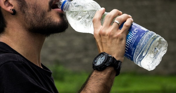 A man drinking from a plastic bottle of water. We need to stop drinking bottled water to save the planet and ourselves.