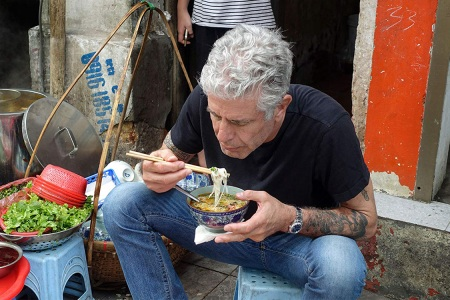 Anthony Bourdain tucking into a bowl of noodles on the set of Parts Unknown, 2013 (Credit: IMDB).