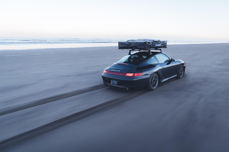 Brock Keen's black Porsche 996 911 with a rooftop tent speeding down the sandy beach next to the ocean