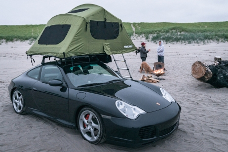 A black 2004 Porsche 996 C4S, or Porsche 911, with a green Yakima rooftop tent owned by Brock Keen of Instagram handle @996roadtrip sitting on a beach with two women in the background next to a campfire