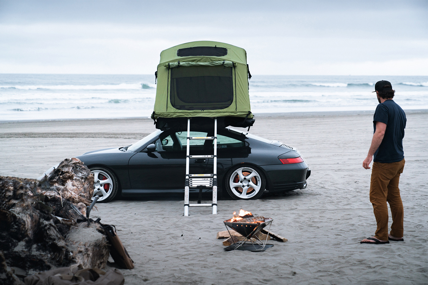 A black Porsche 911 with a green Yakima rooftop car camping tent with a ladder coming down the side sitting next to the ocean on a beach while owner Brock Keen of Instagram account @996roadtrip stands to the right