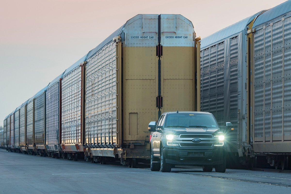 electric ford f-150 pickup towing train cars and trucks