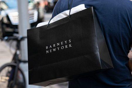 A man carries a Barneys New York shopping bag. (Drew Angerer/Getty)