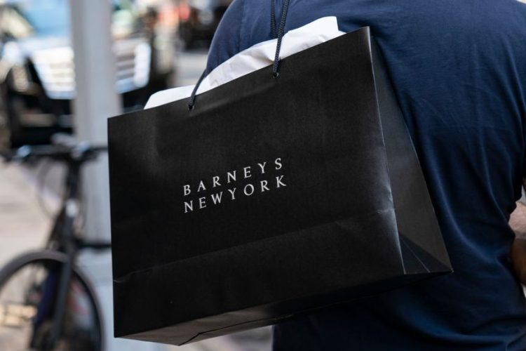 A man carries a Barneys New York shopping bag. (Drew Angerer/Getty)