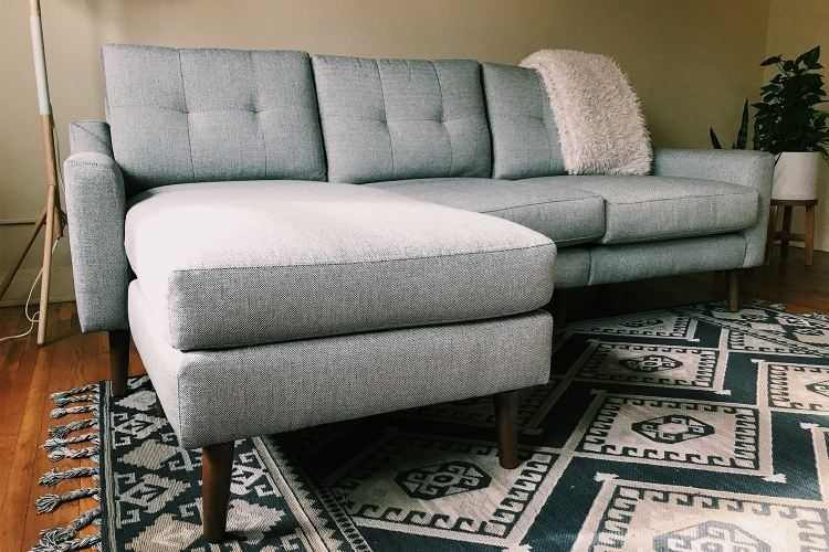 A close-up photo of a Burrow Nomad Sofa Sectional Couch in an apartment on top of a rug with a blanket draped over the back