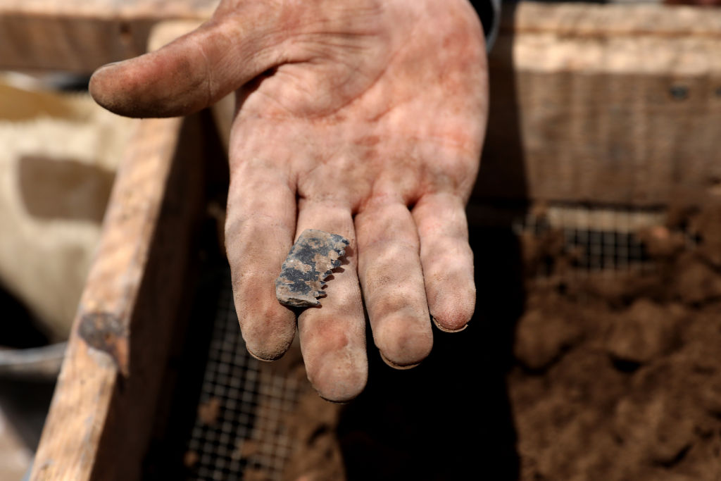A Palestinian excavator holds on July 16, 2019, a flint stone blade found in the rubble at the archeological excavation site of a settlement from the Neolithic Period (New Stone Age), discovered during archaeological excavations by the Israel Antiquities Authority near Motza Junction, about 5km west of Jerusalem. - The settlement is the largest known in Israel from that period and one of the largest of its kind in the region. (Photo by GALI TIBBON / AFP)
