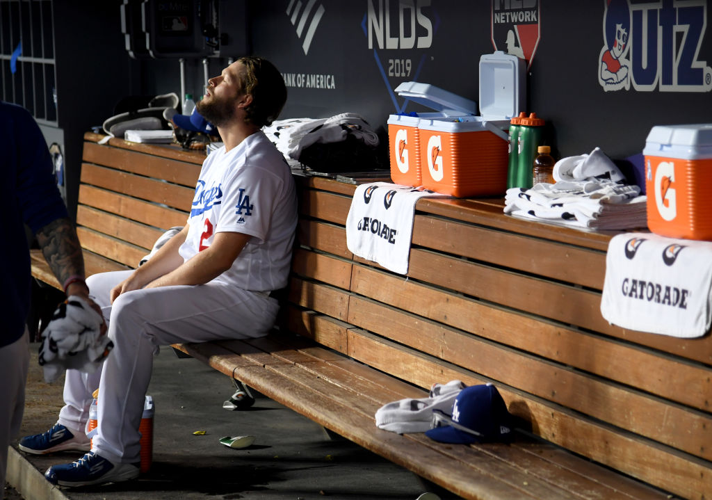Clayton Kershaw of the Los Angeles Dodgers sits in the dug out after leaving the game after giving up back to back home runs in the eighth inning of game five of the National League Division Series against the Washington Nationals at Dodger Stadium on October 09, 2019 in Los Angeles, California. (Photo by Harry How/Getty Images)