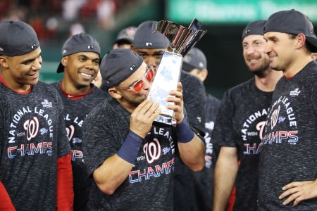 Gerardo Parra #88 of the Washington Nationals celebrates with the trophy after winning game four and the National League Championship Series against the St. Louis Cardinals at Nationals Park on October 15, 2019 in Washington, DC. (Photo by Rob Carr/Getty Images)