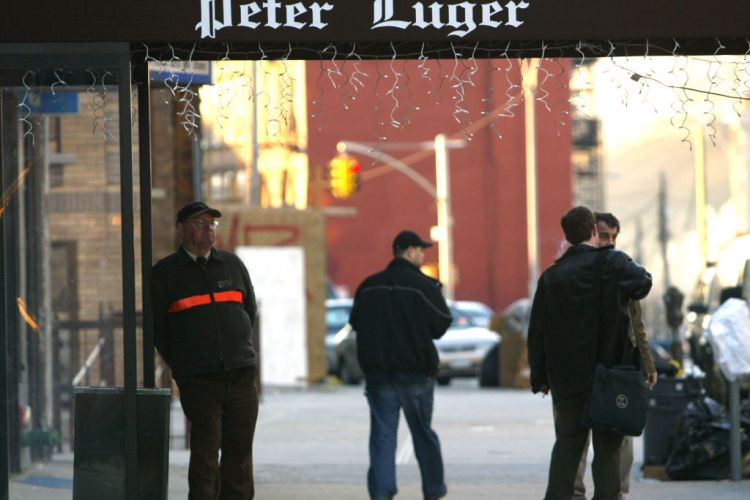 People walk past the Peter Luger steakhouse December 29, 2003 in New York City. (Photo by Spencer Platt/Getty Images)