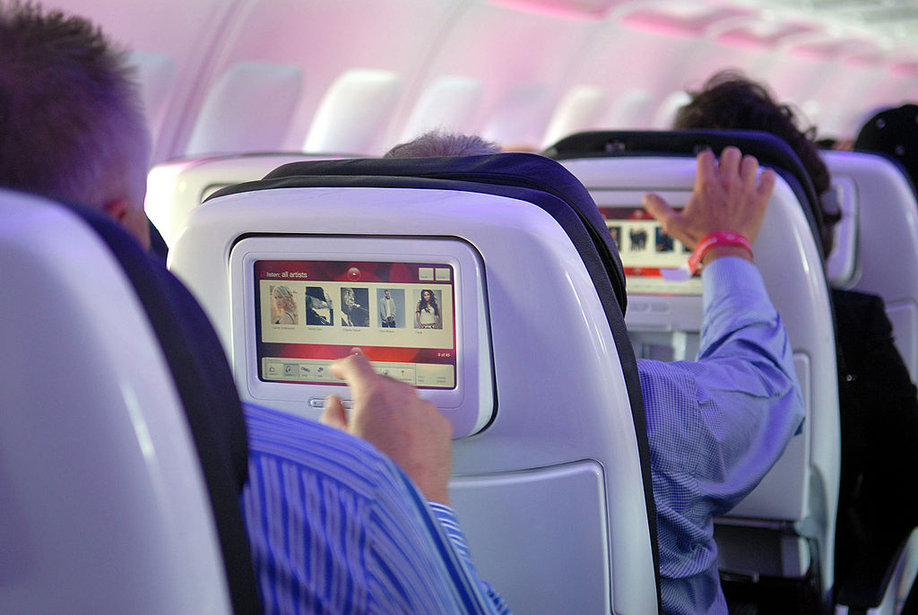 Passengers try out Virgin America airlines' in-flight entertainment system which includes on-demand movies, television, video games, music and onboard chat rooms during the first flights of Virgin America from Los Angeles and New York to its base of operations in San Francisco, California, Wednesday, August 8, 2007. (Photo by Bob Riha/WireImage)