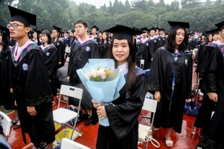 A graduate holding flowers attends the graduation ceremony of Wuhan University with her wife and child on June 22, 2018 in Wuhan, Hubei Province of China. Over 15,000 undergraduates, master and doctoral graduates took part in the commencement ceremony of Wuhan University in the rain on Friday. (Photo by Zhang Chang/China News Service/Visual China Group via Getty Images)