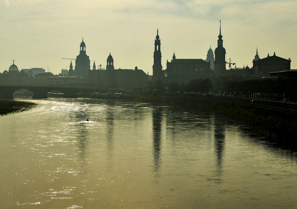 Saxony, Dresden: The silhouette of the old town is reflected in the morning in foggy weather in the Elbe.  (Photo by Jens Kalaene/picture alliance via Getty Images)