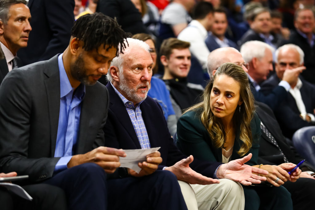 (L-R) Tim Duncan, Gregg Popovitch, and Becky Hammon of the San Antonio Spurs talk during the second quarter of the game against the Minnesota Timberwolves at Target Center on November 13, 2019 in Minneapolis, Minnesota. (Photo by David Berding/Getty Images)