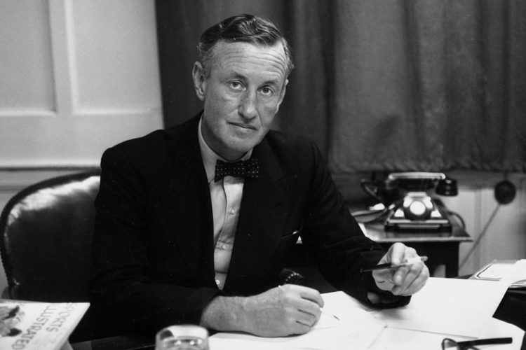 Ian Fleming, British author and creator of James Bond, at his desk. (Photo by Express/Express/Getty)