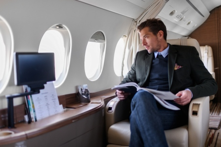 Man sitting inside private jet airplane and looking outside the window while reading a magazine.