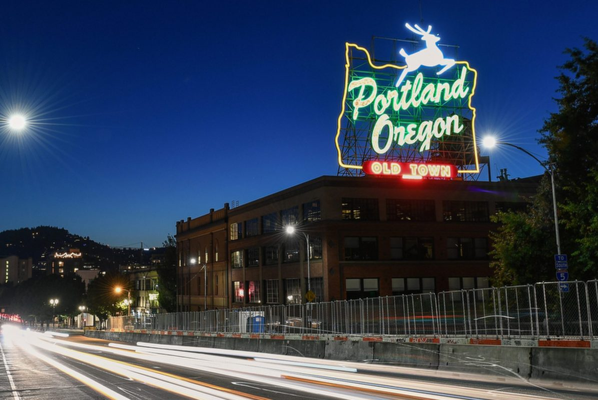 The Portland White Stag sign illuminated at night over Burnside Bridge. (Travel Portland)