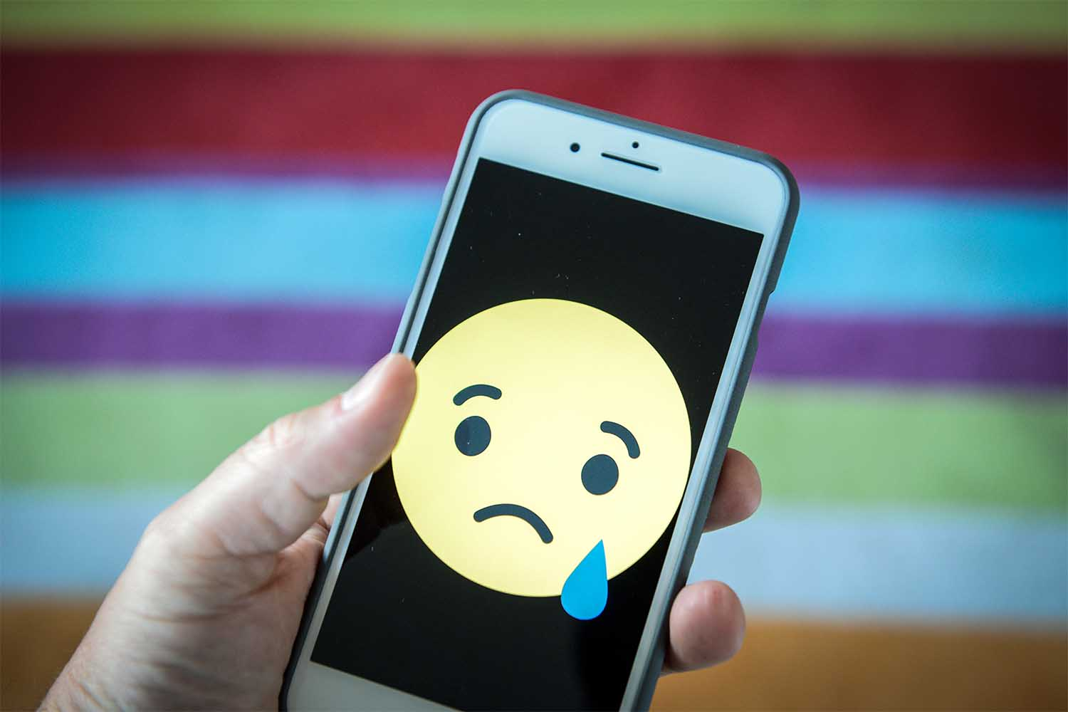 Sad face emoji on a phone